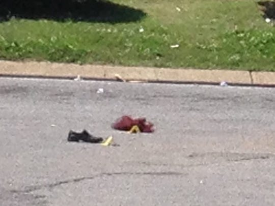 A closer view of the shoe and wig left behind after a shooting.