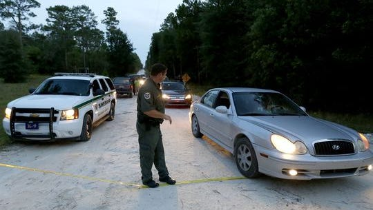 A Gilchrist County, Fla., sheriff's deputy lowers the yellow tape to let vehicles through at the scene of a shooting on Thursday, Sept. 18, 2014, in Bell, Fla.