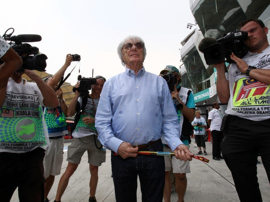 President and CEO of Formula One management Bernie Ecclestone, center, walks at the pit area during the second practice session ahead of Sunday's Malaysian Formula One Grand Prix at Sepang International Circuit in Sepang, Malaysia, Friday, March 28, 2014. (AP Photo/Lai Seng Sin)