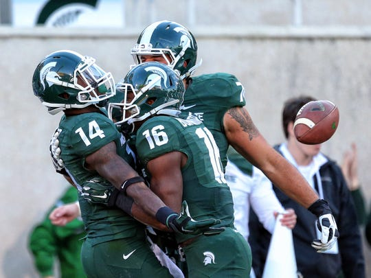 Michigan State Spartans wide receiver Tony Lippett (14) celebrates touchdown catch with Michigan State Spartans wide receiver Aaron Burbridge (16) during the 2nd half of a game at Spartan Stadium.