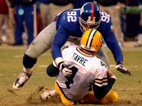 New York Giants defensive end Michael Strahan (92) sacks Green Bay Packers quarterback Brett Favre during the fourth quarter Sunday, Jan. 6, 2002, at Giants Stadium in East Rutherford, N.J. The sack gave Strahan 22.5 sacks for the season surpassing New York Jets Mark Gastineau's NFL record of 22 sacks. (AP Photo/Bill Kostroun)