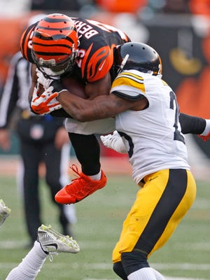 Cincinnati Bengals running back Giovani Bernard (25) is hit in mid-air by Pittsburgh Steelers cornerback Brice McCain (25) during the fourth quarter of their game at Paul Brown Stadium in Cincinnati, Ohio Sunday December  7, 2014. The Enquirer/Gary Landers