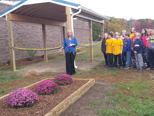 Millside Elementary Principal Melissa Hanners speaks about the development of the outdoor classroom at Algonquin Elementary School as Cheri Soultaire's sixth-grade STEM class looks on.