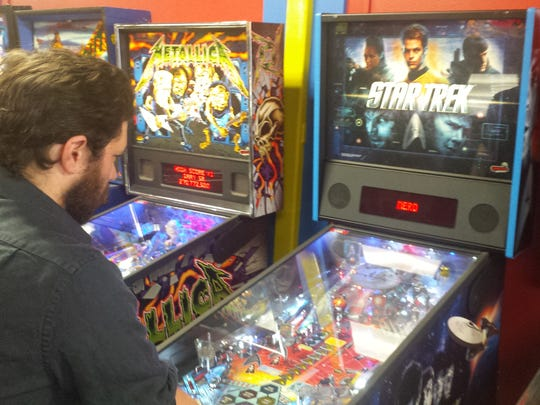 Christian Murray, assistant manager of Yestercades in Somerville, tests one of the pinball machines.