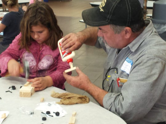 Chloe Vanderpool works with community volunteer Jim Guttmann, grandfather to student Cole Guttmann. Second grade students at Random Lake Elementary School recently participated in a free kid's workshop offered by Home Depot.