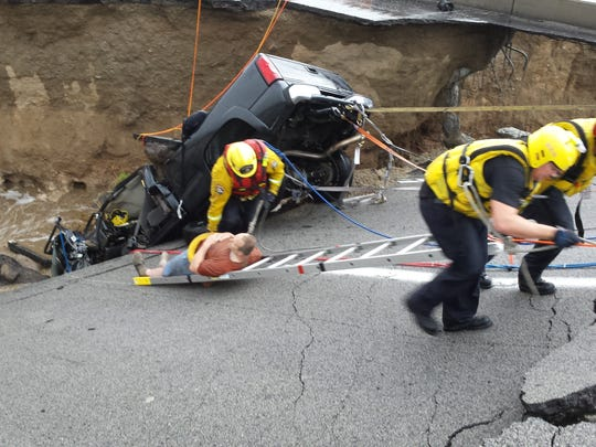 Firefighters pull an injured motorist from a trapped vehicle after the Tex Wash Bridge collapse in July. Four firefighters and two policemen will be given a Medal of Valor award on Tuesday for the rescue.