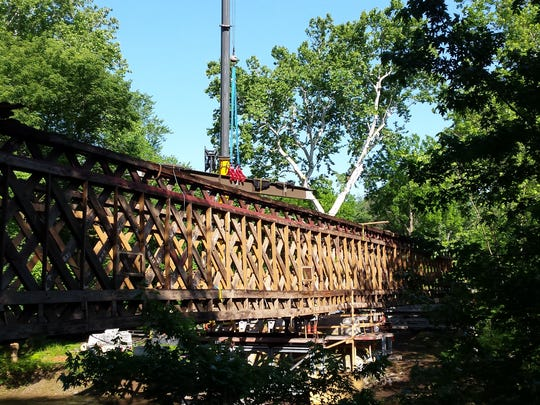 A beam is set during the restoration of the Martins Mill Bridge in June 2015.