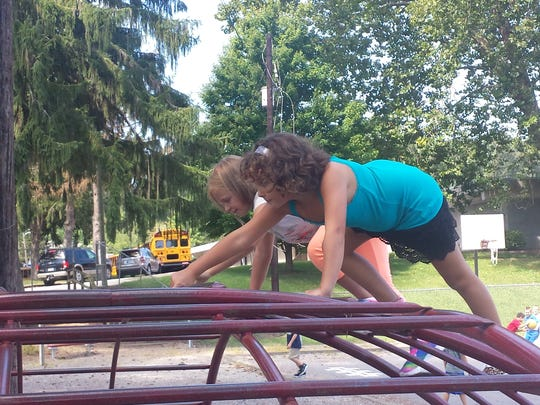 Mara Stout and Leeyna Wilson climb on the playground at Black Mountain Primary on the first day of school