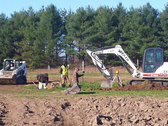 Crews work to lay the foundation for the Meeme livery stable at Manitowoc County Historical Society.