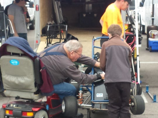 Jack Pachek helps a young midget racer during an event