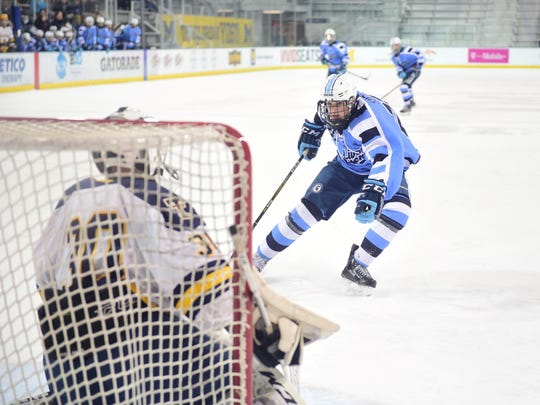 Livonia Stevenson's Josh Suzio (22) cuts in on Trenton goalie Joey Cormier Tuesday night at Yost Ice Arena in Ann Arbor.