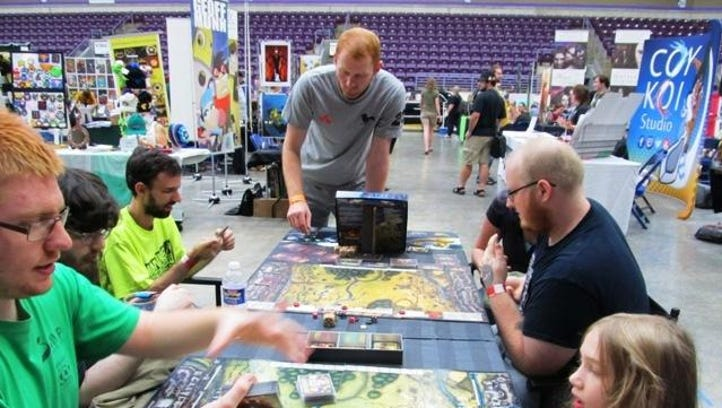 Horseheads native T.J. Dunbar explains the intricacies of his game, Castle Assault at Twin Tiers Comic Con Sunday.