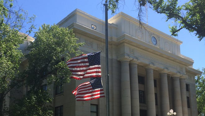 Two American flags fly at half-staff outside the courthouse in Prescott.