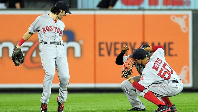 Red Sox outfielders Andrew Benintendi (left) Jackie Bradley, Jr. (center) and Mookie Betts (right) celebrate after beating the Orioles 5-3.