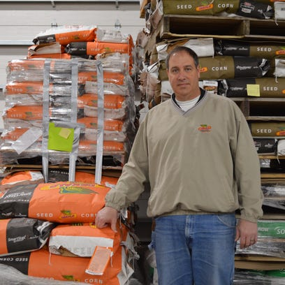 Steve Reinhard poses with seed bags at Reinhard Farms
