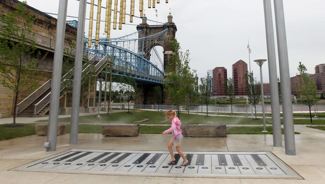Lorenza Rohrkemper, 7, of Harrison, dances across the foot piano in Smale Park.  A section of the park west of the bridge is now open.