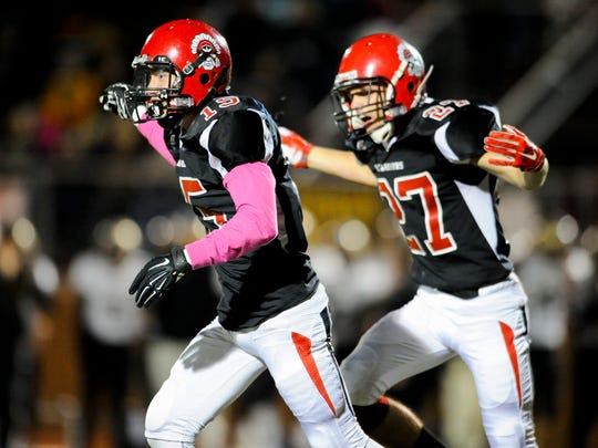Harrison's Jayden Pease (15) and Harrison's Cameron Roberts (27) celebrate during their sectional game against Jasper at Romain Stadium in Evansville, Friday, Oct. 21, 2016.