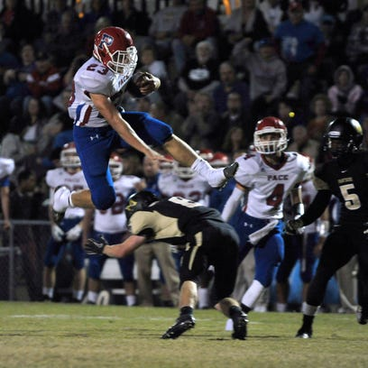 Pace running back Quaide Weimerskirch, left, leaps over a Milton defender on his way to a big gain Friday night as the Patriots traveled to face the Panthers and came away with a 47-7 win.