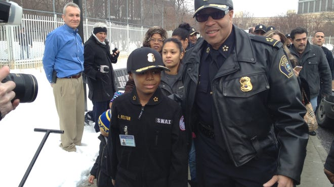 Jayvon Felton walks with Detroit Police Chief James Craig outside the Detroit Public Safety Headquarters on Jan. 31, 2014, after Craig named Jayvon chief for the day. Jayvon, who was joined by his family, is battling leukemia.