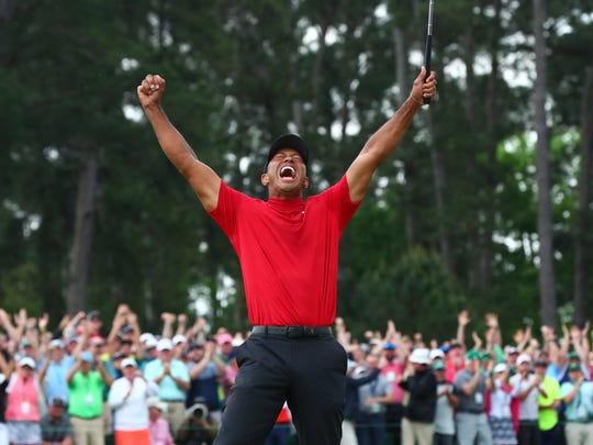 Apr 14, 2019; Augusta, GA, USA; Tiger Woods celebrates after making a putt on the 18th green to win The Masters golf tournament at Augusta National Golf Club. Mandatory Credit: Rob Schumacher-USA TODAY Sports