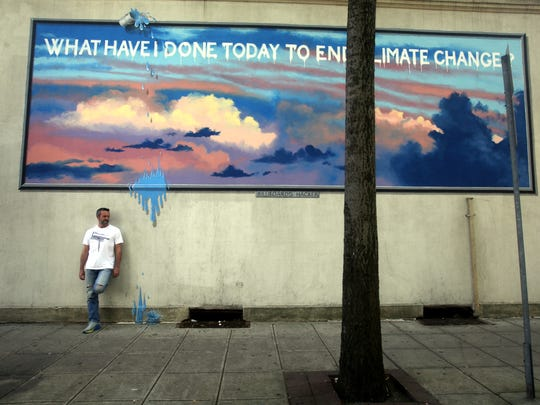 New Rochelle artist Patrick Bancel stands under one of several murals he has painted in downtown New Rochelle.