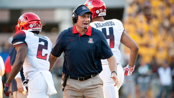 Arizona Wildcats head coach Rich Rodriguez congratulates wide receiver Tyrell Johnson (2) and wide receiver David Richards (4) after scoring against the Arizona State Sun Devils during the fourth quarter of the territorial cup at Sun Devil Stadium. The Sun Devils won 52-37.