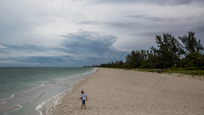 A man walks along the beach near Naples Pier on Monday, May 14, 2018. The beaches were nearly empty after a rainstorm passed through the area.