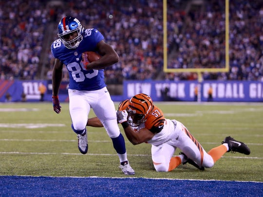 Giants' Jerell Adams stays out of the grasp of Bengals' Vincent Rey to score in the first quarter of Monday night's game.