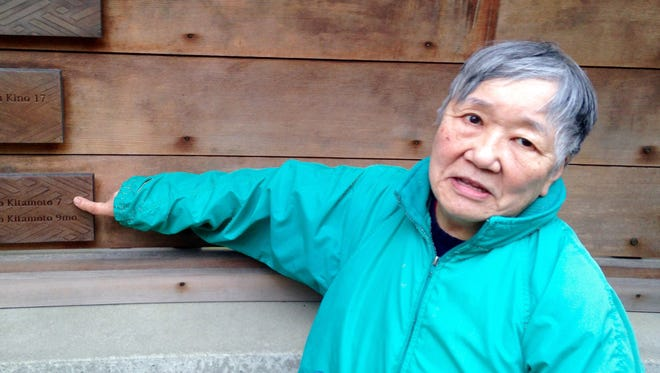 Lilly Kodama points to her name on the Japanese American Exclusion Memorial story wall on Bainbridge Island. Kodama, who participated in a park cleanup Sunday, was 7 years old when her family was removed to an internment camp.
