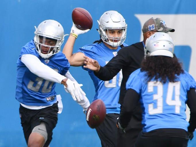 Lions cornerback Antwuan Davis swats away the ball,