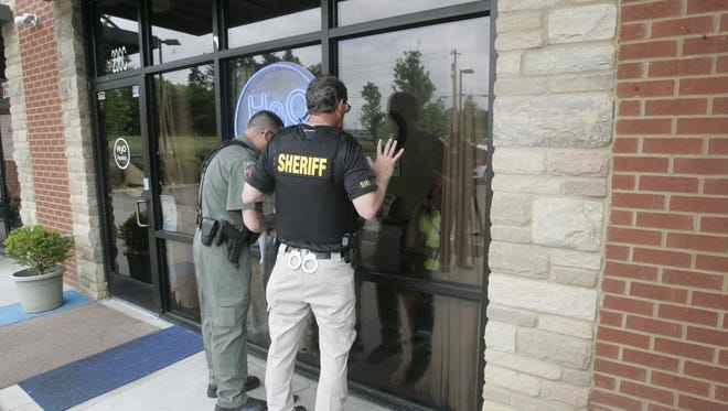 Sgt. Whit Davis and Capt. Nathan Pagel of the Rutherford County Sheriff's Office read Keith Van de Castle the restraining order they are serving.