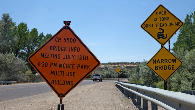 A sign posted alongside County Road 5500 informs residents of a meeting regarding the county's plan to replace the aging bridge over the San Juan River.