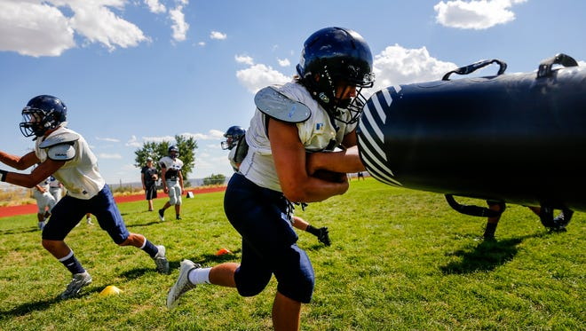 At right, Piedra Vista High School running back McKay Cook carries the ball during practice, Wednesday, Aug. 9, 2017 at Piedra Vista High School in Farmington.
