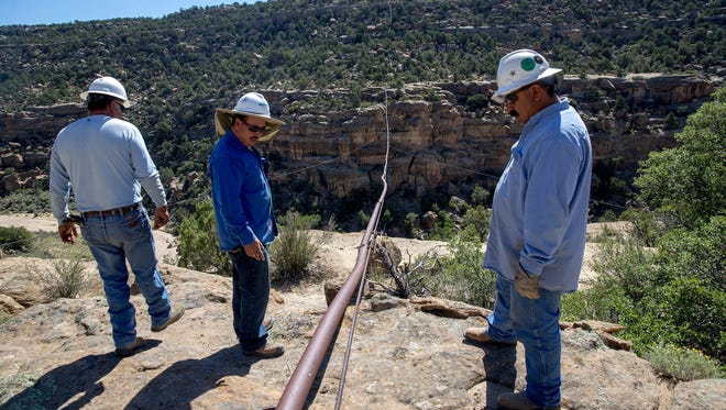 Harpole Construction Inc., workers look over a natural gas pipeline Aug. 14 above Simon Canyon near Navajo Dam.