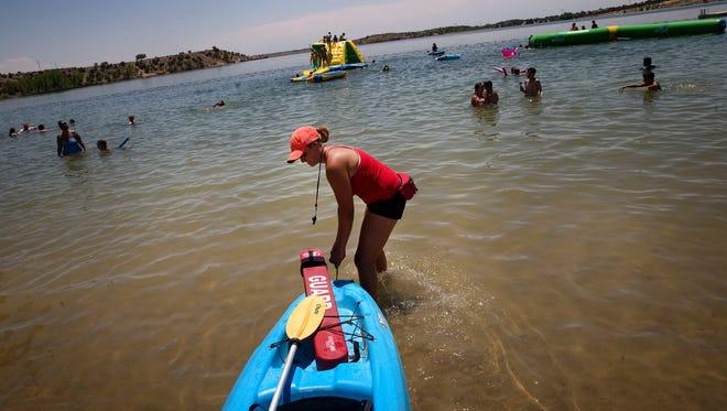 Lifeguard Emilee Lucero prepare for her patrol in her kayak June 26 at the Beach at Farmington Lake.