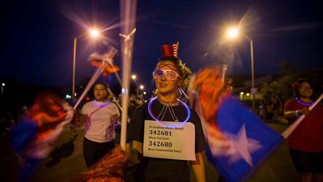 Piedra Vista High School's Rebecca Martinez marches with members of the Farmington and Piedra Vista high school bands during last year's Farmington Rotary Electric Light Parade along Main Street. The annual parade is one of several Freedom Days events taking place over the next several days.