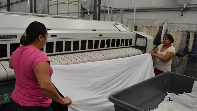 Workers feed sheets into a pressing machine at Quality Linen Service in Salisbury.