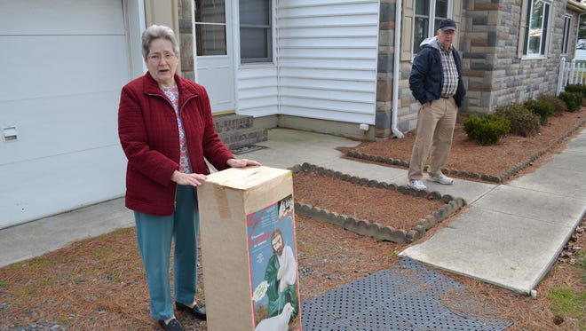 Carolyn Merrill holds the storage box for a nativity scene figure that was stolen from in front of her Princess Anne home. Her husband, Sidney, stands in the background.