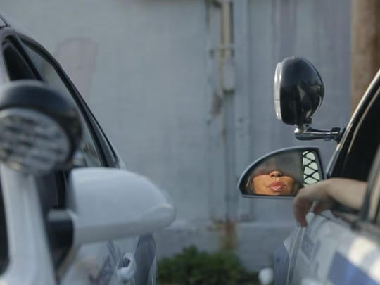 Calderon is reflected on the patrol car's side mirror as she talks to officer Jen Tarbell.