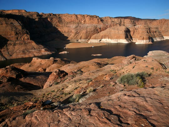 Houseboats can be seen beached on the far shore of Lake Powell beneath the steep canyon walls on Oct. 19, 2014.