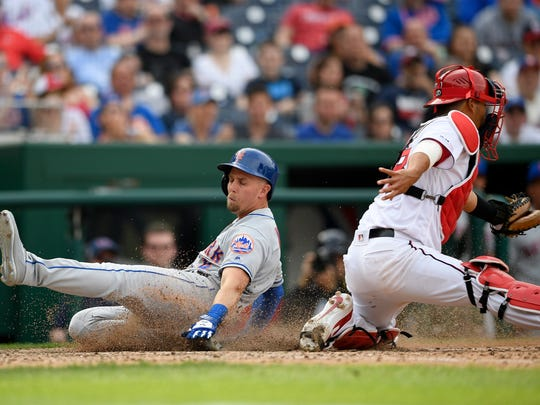 New York Mets' Jeff McNeil, left, slides home to score a run against Washington Nationals catcher Kurt Suzuki, right, during the ninth inning of a baseball game, Saturday, March 30, 2019, in Washington. Mets win 11-8. (AP Photo/Nick Wass)
