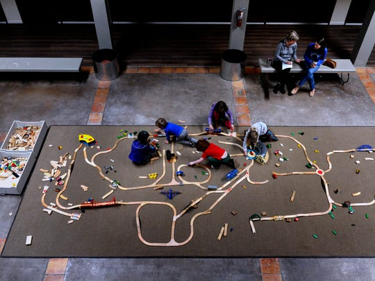 Children create their own railroads in the lobby outside the Abilene Society of Model Railroaders new home Saturday. The wooden set provides a relief for tiny fingers forbidden to touch the more elaborate setup in the club's new home at 598 Westwood.