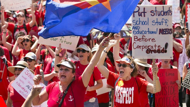 Anna Cicero, (center left) a teacher and school counselor at Mesa Public Schools, waves an Arizona flag, as Julie Cieniawski, (center right) a teacher at Scottsdale Unified School District, holds a sign at a RedForEd rally at the Arizona Capitol in Phoenix on the second  day of the Arizona teacher walkout on Friday, April 27, 2018.