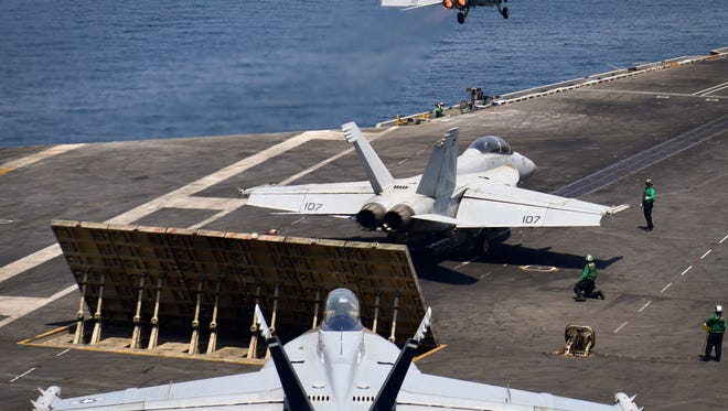 An F/A-18F Super Hornet launches from the flight deck of the aircraft carrier USS Nimitz while other aircraft prepare to launch on Saturday in the Arabian Gulf.