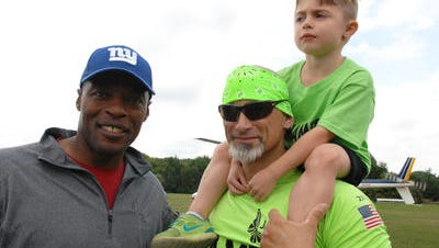 Former New York Giants star Mark Collins (left) with Jim Raffone and his son Jamesy at last month's push-ups challenge.