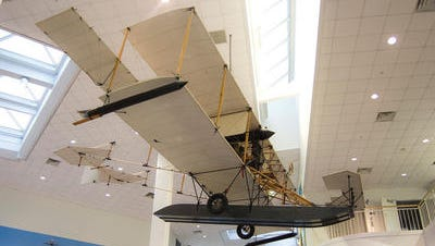 An exact replica of the Curtiss A-1 Triad, which was the first aircraft procured by the U.S. Navy, hangs in the National Naval Aviation Museum.