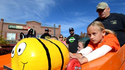Emma Eisenhauer, 9, of Sparks places her bumble bee-painted pumpkin on a ramp to race at the Pumpkin Derby at the annual Pumpkin Palooza at Victorian Square on Sunday, Oct. 26, 2014.