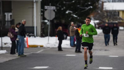 South Western High School senior Ben Schott crosses the finish line during the 23rd annual Community 5K Turkey Trot in New Oxford on Thursday Nov. 27, 2014. Schott was the overall winner of the race coming in first place.