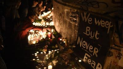 "Candles have been lit at a pop-up memorial set near the cafe ""Bonne biere,"" one of the sites of the attacks in Paris on Friday. Islamic State jihadists claimed a series of attacks by gunmen and suicide bombers in Paris that killed at least 128 people."