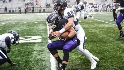 Wesley's Mike Sabino attempts to corral a Mount Union defender in Saturday's NCAA Division III quarterfinal. Mount Union defeated Wesley 56-35.